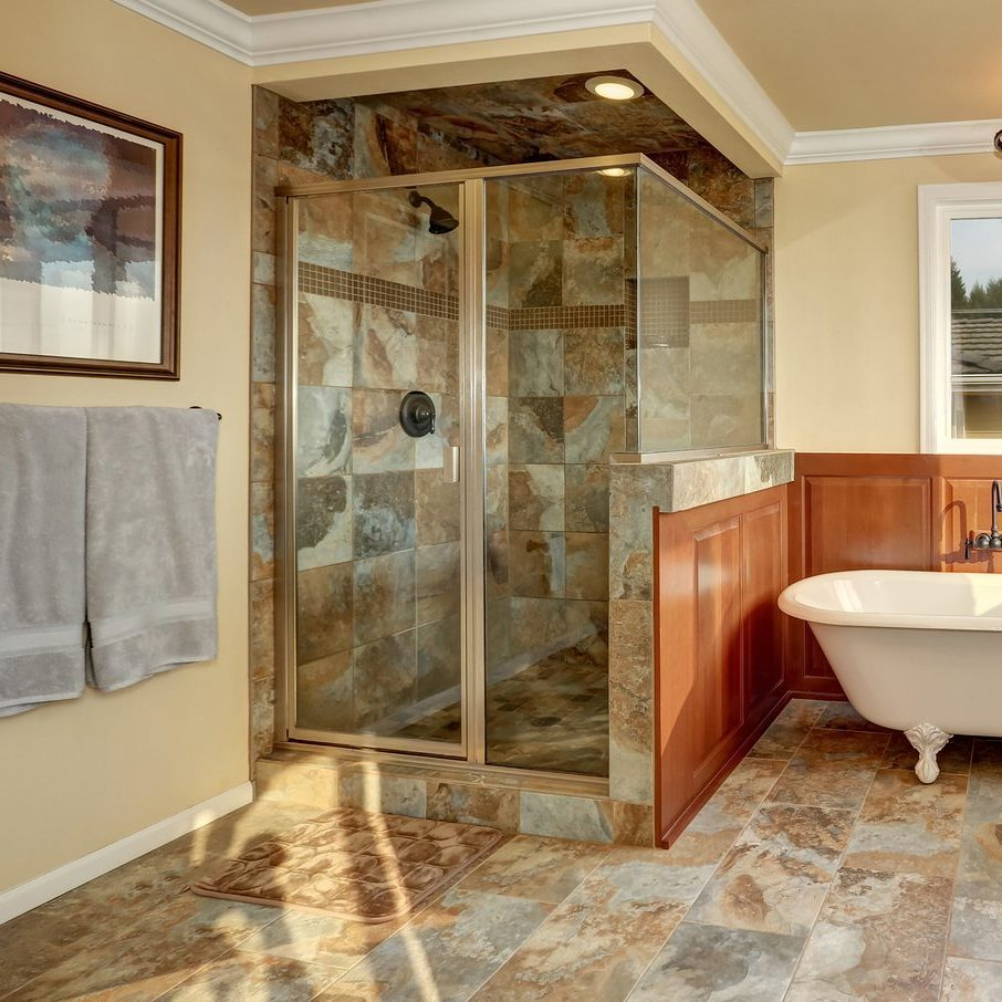 Bathroom with natural stone tile and beige walls. Glass corner shower freestanding white tub and double sink vanity bathroom. Northwest USA